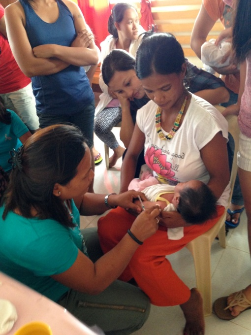 Maboy holding baby Zanelle as she gets her BCG vaccination.